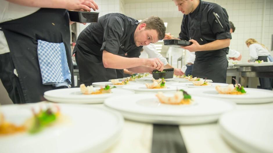 Koch beim anrichten  Edles Fünf-Gänge-Menu: Anrichten, auftischen, Dampf ablassen